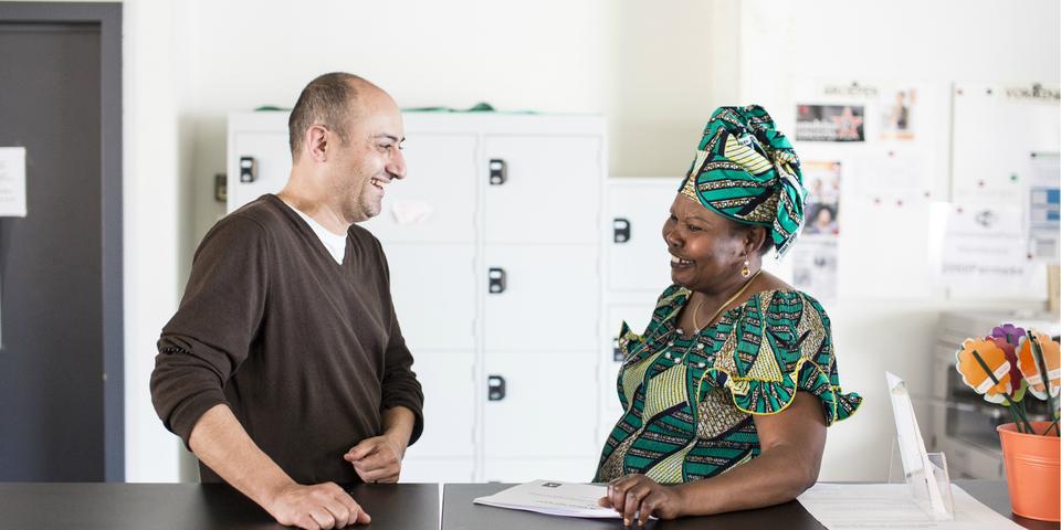 Man en vrouw hebben gesprek in een buurtsecretariaat.