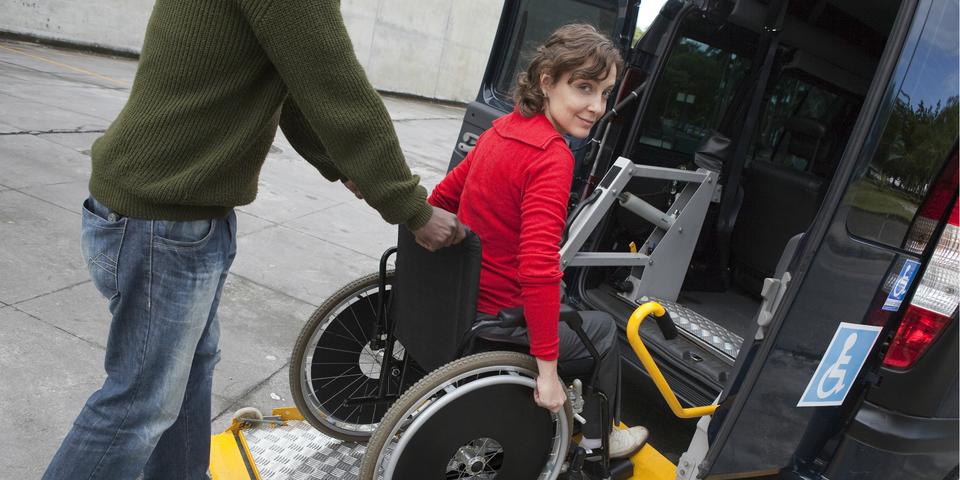 Vrouw in rolstoel neemt taxi.