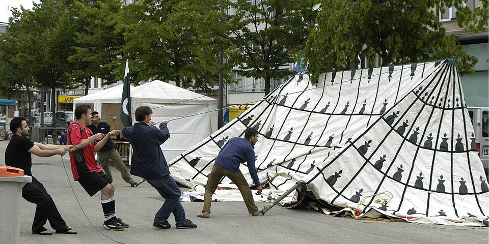 Vrijwilligers zetten een tent op.