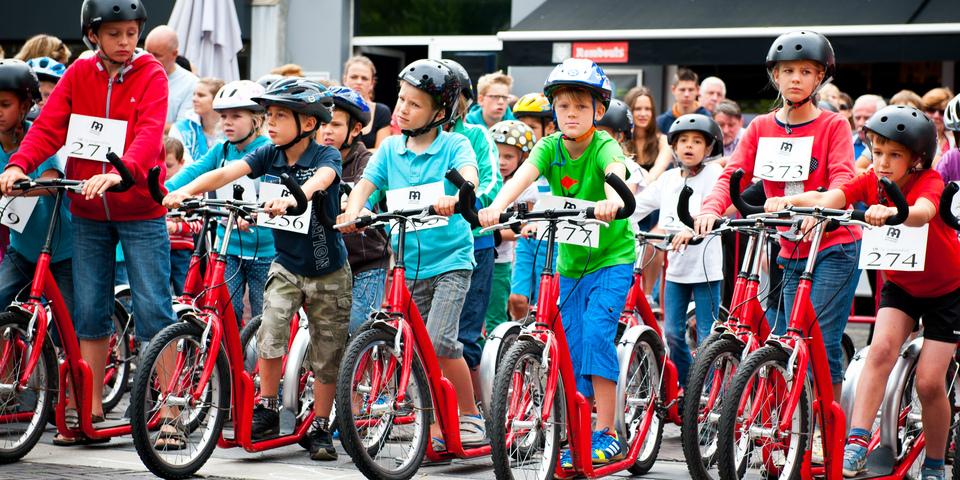 Kinderen staan aan de start van de trotinettenkoers
