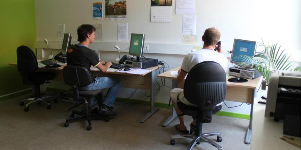 Leden van een vereniging werken aan de computer in een buurtsecretariaat.