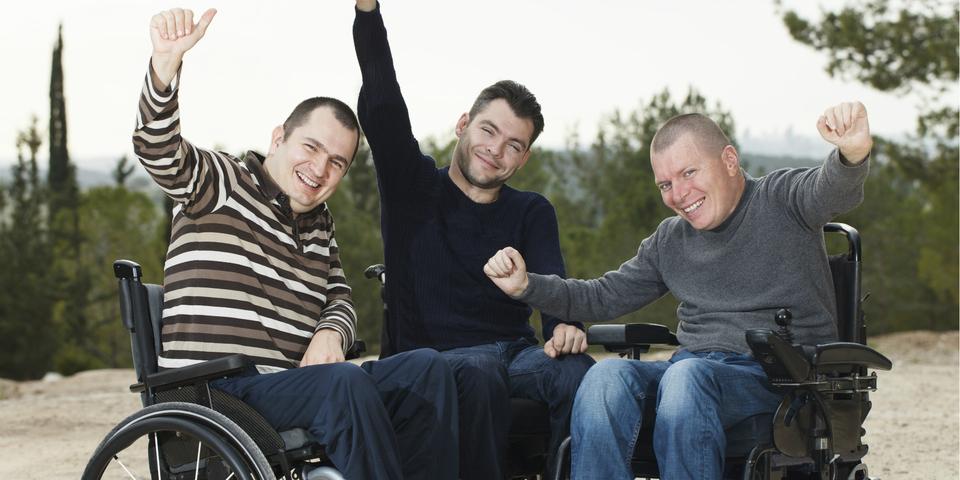 Drie mannen in een rolstoel.